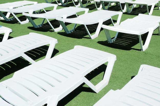 Białe leżaki na zielonym sztucznym trawniku