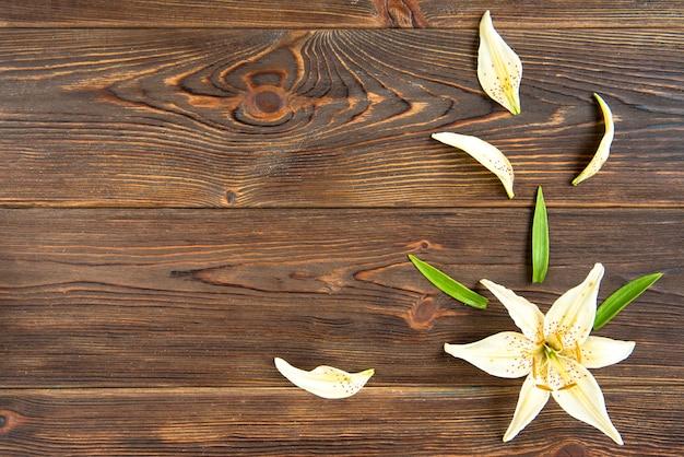 Białe lilie kwitną na ciemnym drewnie