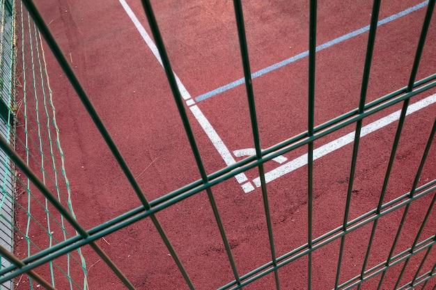Białe linie oznakowania zewnętrznego boiska do koszykówki ogrodzone metalowym ogrodzeniem ochronnym