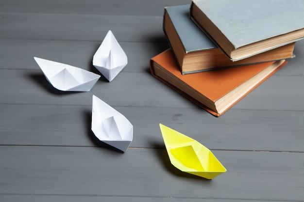 Białe łódki idą na żółto obok książek na szarym tle