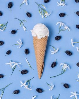 Białe lody waniliowe otoczone jeżynami i kwiatami
