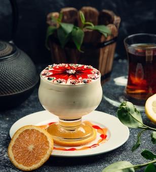 Białe lody z syropem truskawkowym na stole
