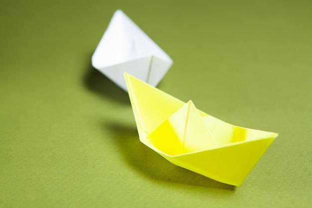 Białe łodzie idą za żółtym na zielonym tle