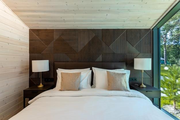 Białe łóżko, kołdra i poduszki w drewnianej sypialni. sypialnia hotelowa. wygodne łóżko z miękkim kocem w stylowym pokoju