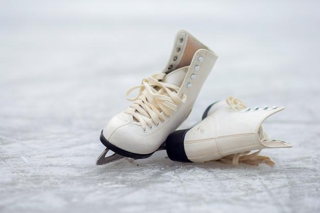 Białe łyżwy figurowe leżą na otwartym lodowisku