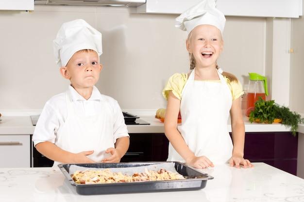 Białe małe dzieci w strojach szefa kuchni z pyszną pizzą w kuchni