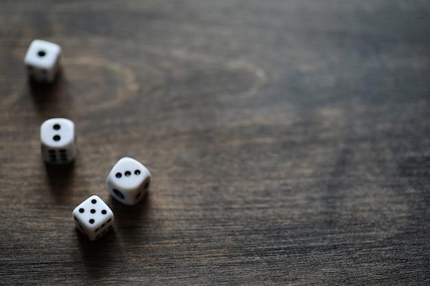 Białe małe kostki na brązowym drewnianym stole z teksturą