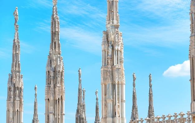 Białe marmurowe posągi na dachu słynnej katedry duomo di milano na placu w mediolanie, włochy
