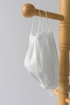 Białe maski medyczne wiszące na drewnianym wieszaku