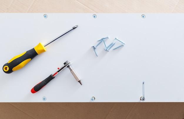 Białe meble w procesach kolekcjonerskich. narzędzia ręczne śrubokręt na półce szafki. przeprowadzki, majsterkowanie, naprawa i renowacja mebli. widok z góry na kartonowym tle.