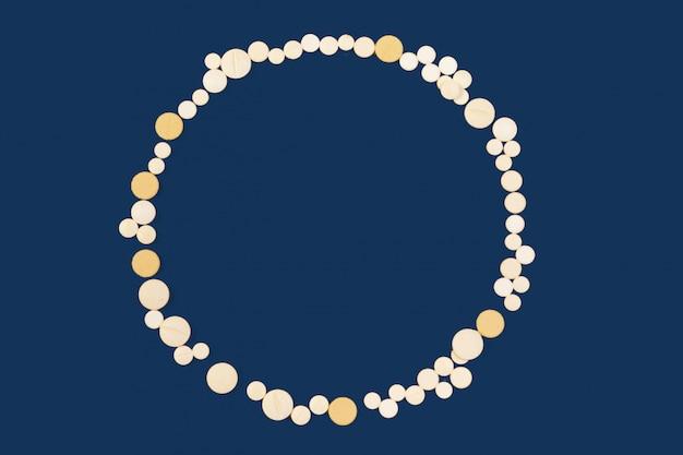 Białe medyczne pigułki na klasycznym błękitnym koloru tle