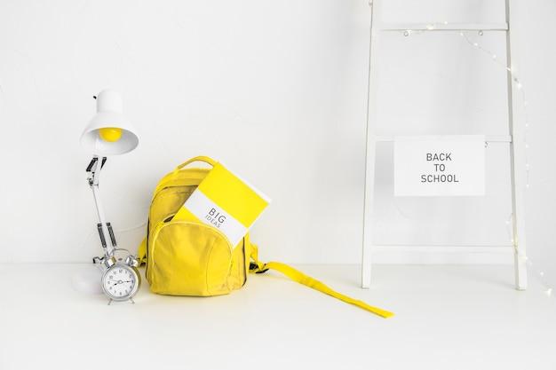Białe miejsce pracy dla ucznia z żółtą torbą i budzikiem