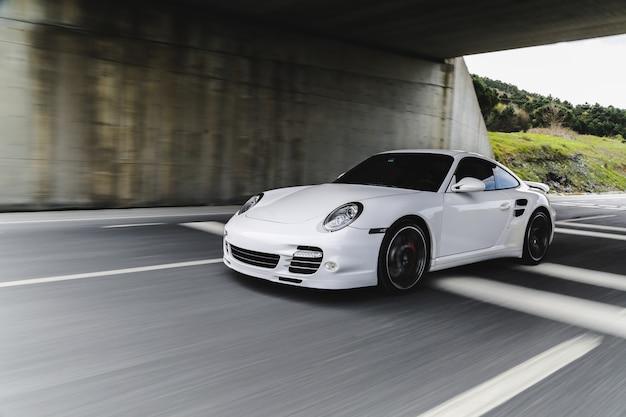 Białe mini coupe na drodze.
