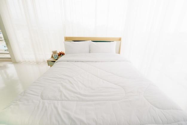 Białe minimalistyczne wnętrze sypialni w godzinach porannych ze światłem słonecznym.
