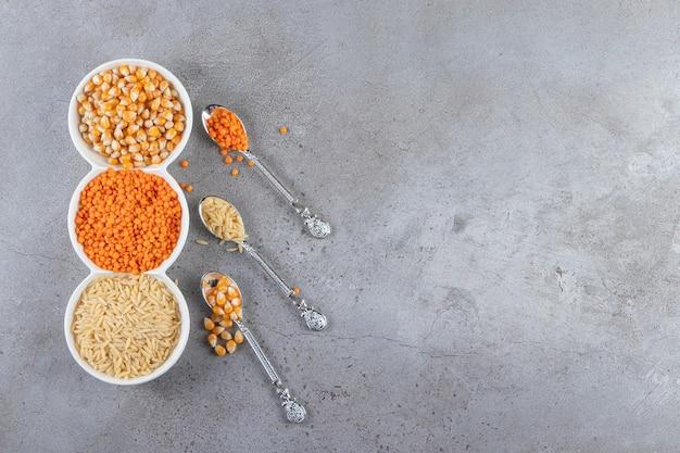 Białe miski z surowym ryżem, soczewicą i kukurydzą na kamiennym tle.