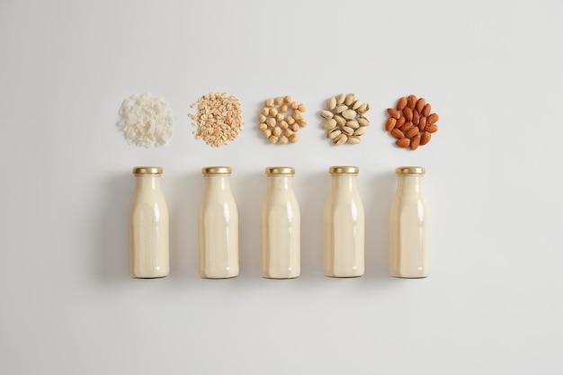 Białe mleko roślinne z orzecha kokosowego, owsa, orzecha laskowego, pistacji i migdałów. składniki do przygotowania napoju wegetariańskiego. produkt zawiera dużą ilość białka, witaminy d, wapnia. zdrowy napój
