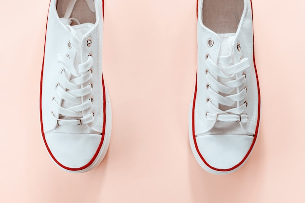 Białe modne białe trampki na kremowym brzoskwiniowym tle. leżał płasko, widok z góry. miejsce na tekst. minimalistyczna kompozycja stylu.
