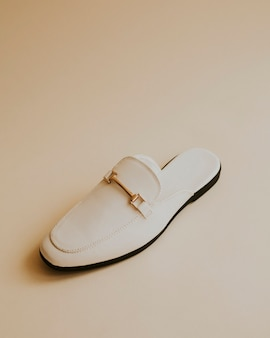 Białe mokasyny klapki na beżowym tle