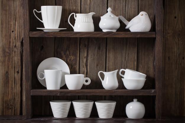 Białe naczynia kuchenne na starej ciemnej drewnianej szafce
