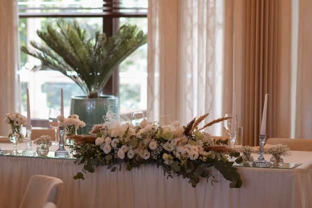 Białe obrusy z przezroczystymi wazonami i białymi kompozycjami z chryzantem i paproci