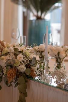 Białe obrusy z przezroczystymi wazonami i kompozycjami z białych kwiatów i paproci. złote talerze, peavh serwetki, numery stołów i lusterka na środku.
