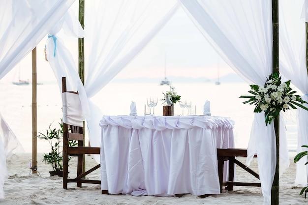 Białe odcienie romantyczna luksusowa kolacja na tropikalnej plaży o zachodzie słońca dekorowany stół z kieliszkami do winorośli