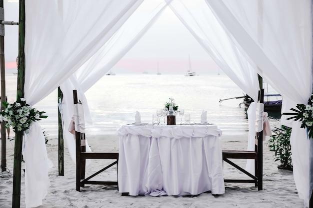 Białe odcienie romantyczna luksusowa kolacja tropikalna plaża o zachodzie słońca zdobiony stół z winoroślą i krzesłami