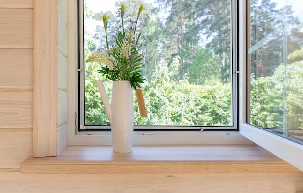 Białe okno z moskitierą w rustykalnym drewnianym domu z widokiem na ogród, las sosnowy. bukiet białych irysów i kwiatów łubinu w stylowej skandynawskiej konewce na parapecie