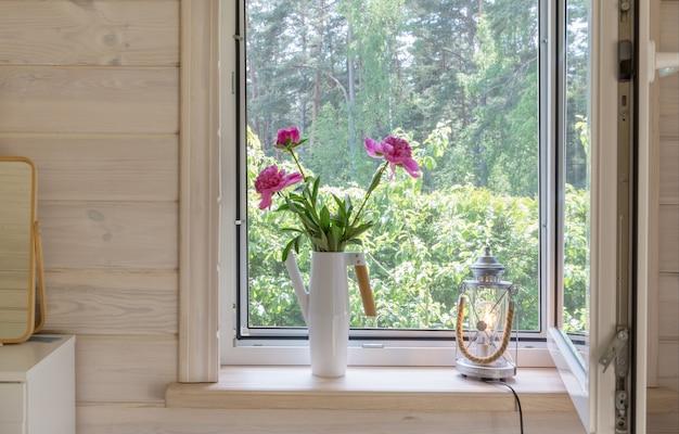 Białe okno z moskitierą w rustykalnym drewnianym domu z widokiem na ogród, las sosnowy. bukiet różowych piwonii w stylowej skandynawskiej konewce na parapecie