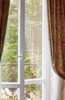 Białe okno z widokiem na zielone drewno