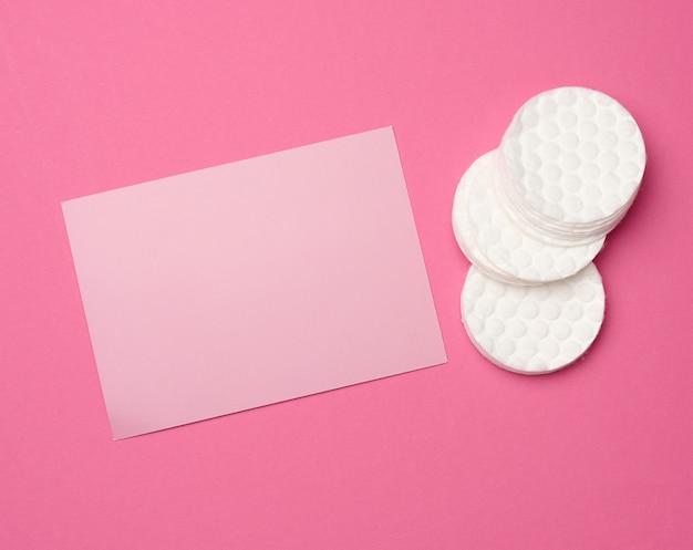 Białe okrągłe puste waciki do demakijażu i pusta kartonowa wizytówka do pisania tekstu, reklamy i promocji