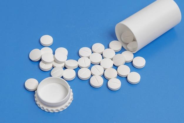 Białe okrągłe tabletki i plastikowa butelka na tabletki na niebieskim tle