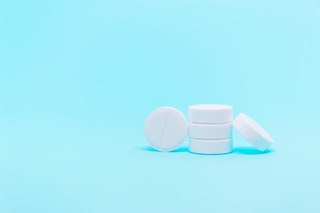 Białe okrągłe tabletki na niebieskim tle zbliżenie z miejscem na kopię