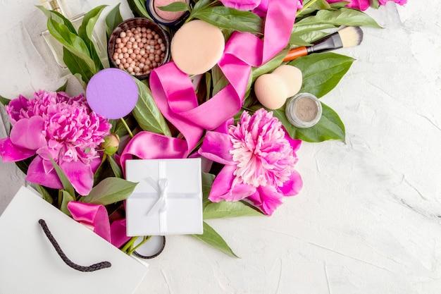 Białe opakowanie upominkowe, zapakowane na prezent, kosmetyki dekoracyjne, różowa wstążka i różowe piwonie. widok z góry.