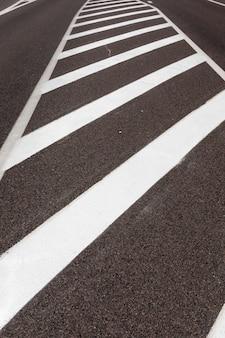 Białe oznaczenia na drodze zapewniające bezpieczeństwo i regulację ruchu samochodów, część złożonego systemu regulacji ruchu, który zapewnia bezpieczeństwo na drodze