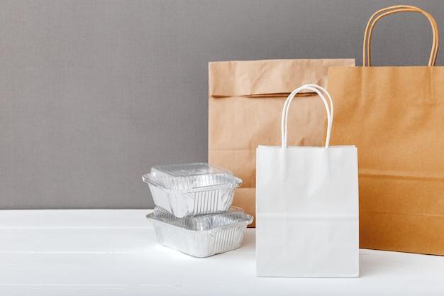 Białe papierowe torby rzemieślnicze i pojemniki na żywność na białym stole szarym tle. usługa dostawy jedzenia.