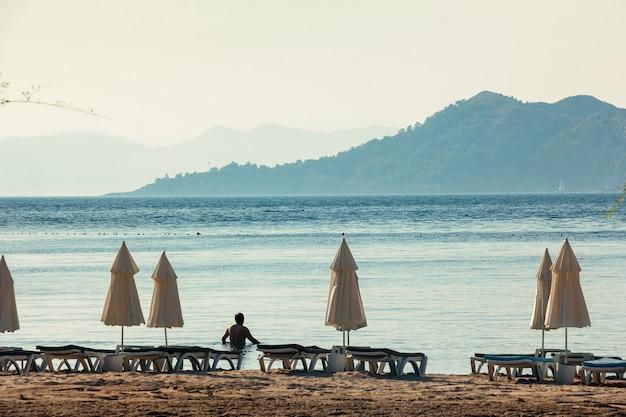 Białe parasole, błękitne morze i duże góry na horyzoncie