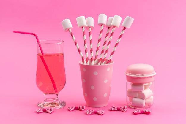 Białe pianki marshmallows z różowymi patyczkami wraz z napojem na różowym biurku, cukier słodki kolor