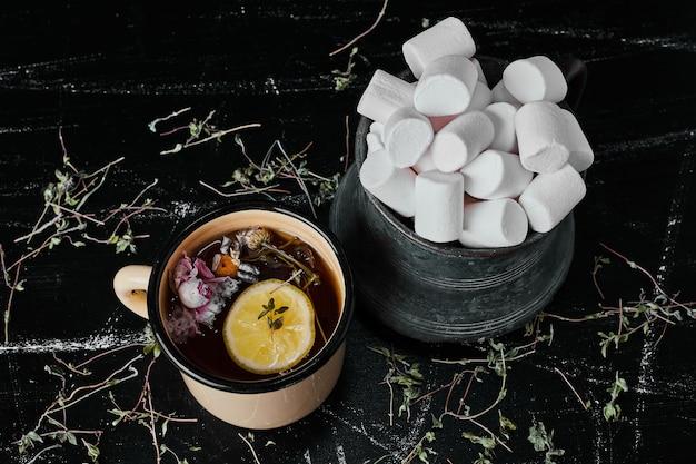 Białe pianki w metalowej filiżance z herbatą ziołową.