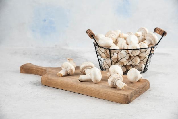 Białe pieczarki w metalowej tacy na drewnianym półmisku.