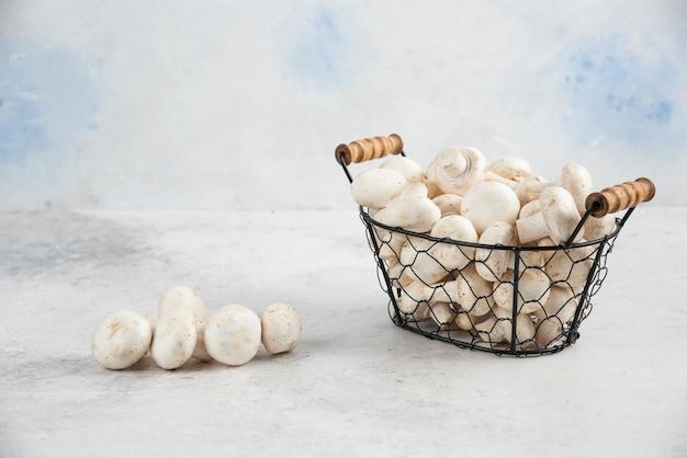 Białe pieczarki w metalowej tacy na marmurowym stole.