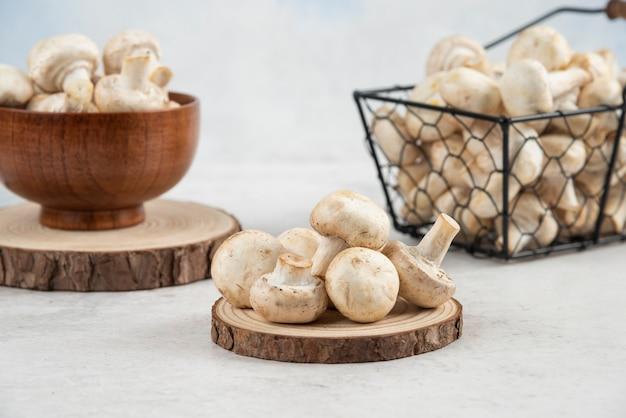 Białe pieczarki w metalowym koszu, wewnątrz drewnianego kubka i na drewnianej desce.