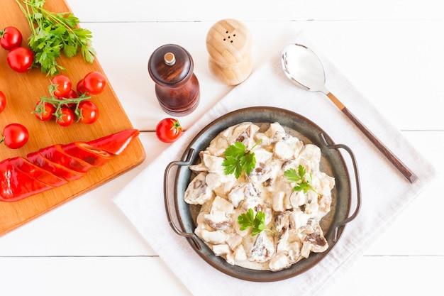 Białe pieczarki z kwaśną śmietaną i natką pietruszki, przyprawami i dodatkami dla wzmocnienia smaku. widok z góry.