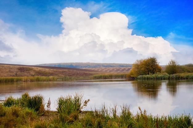 Białe piękne kręcone chmury w błękitne niebo nad rzeką. jesienny krajobraz z rzeką