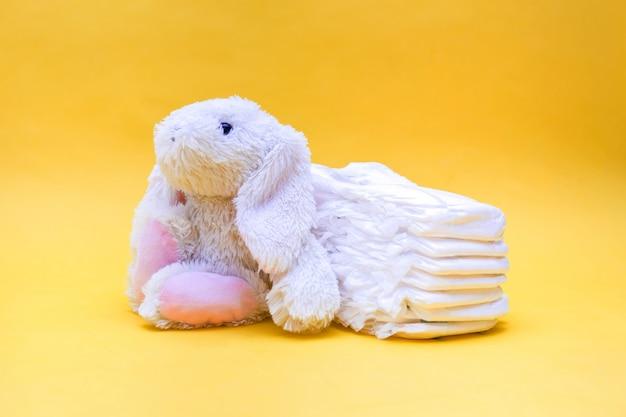 Białe pieluchy i królik na żółtej przestrzeni. królik zabawka na żółtej przestrzeni. pieluchy dla dziecka z rzędu na przestrzeni z wolną przestrzenią.