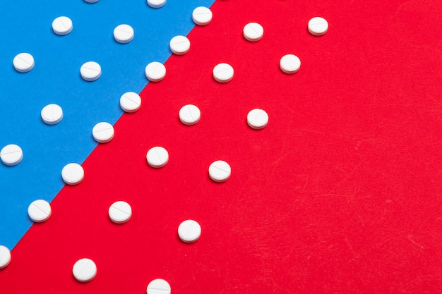 Białe pigułki medyczne na dwóch kolorach czerwonym i niebieskim tle