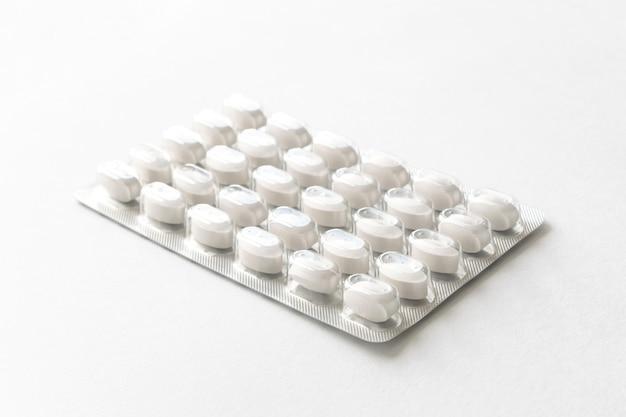 Białe pigułki tabletki w opakowaniu na białym