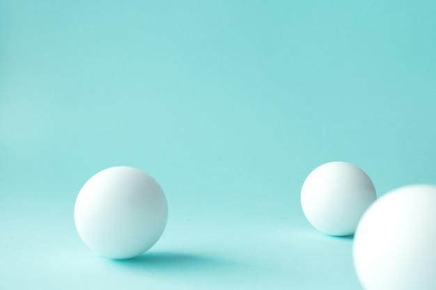 Białe piłki do ping-ponga na miętowo-zielonym stole