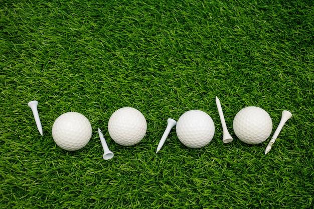 Białe piłki golfowe i białe trójniki są na zielonej trawie