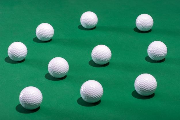 Białe piłki golfowe rozrzucone na zielonym dywanie